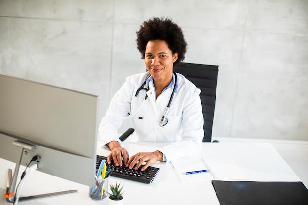 Vrouwelijke afrikaanse amerikaanse arts die witte laag met stethoscoop draagt die achter bureau in het bureau zit