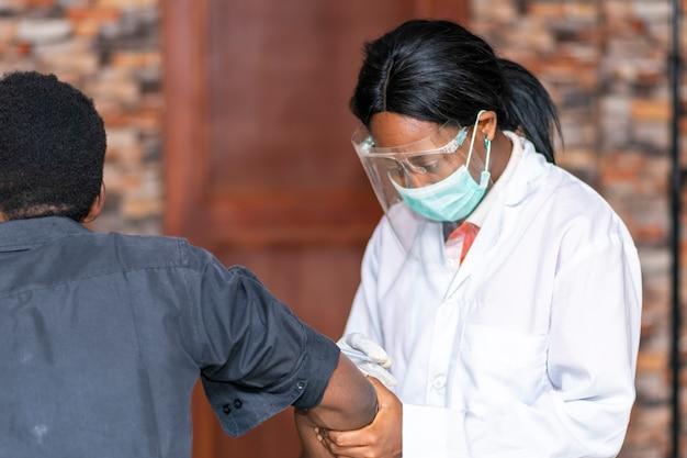 Vrouwelijke afrikaanse arts die een vaccin toedient