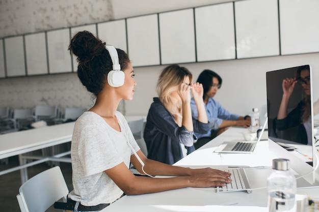 Vrouwelijke afrikaanse call center werknemer met behulp van computer en praten met collega's. binnenportret van managers van internationaal bedrijf die in groot kantoor werken.