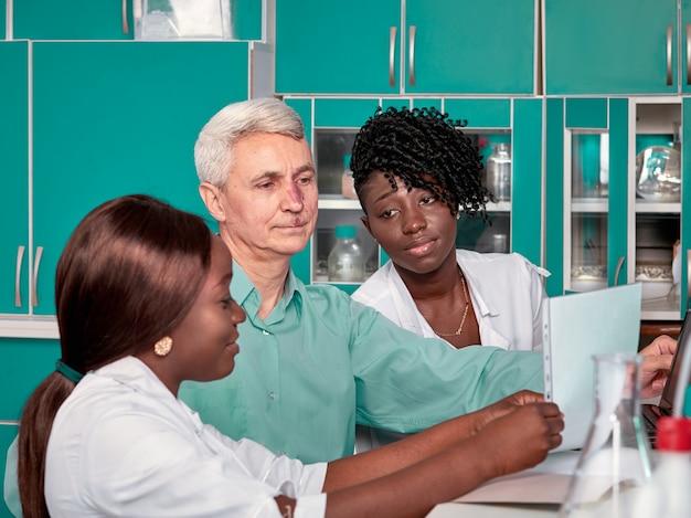 Vrouwelijke afrikaanse medische studenten of jonge afgestudeerden bespreken met blanke senor mannelijke groepsleider in onderzoek of medisch laboratorium. op zoek naar medicijnen, ontwikkeling van een vaccin om de pandemie te bestrijden