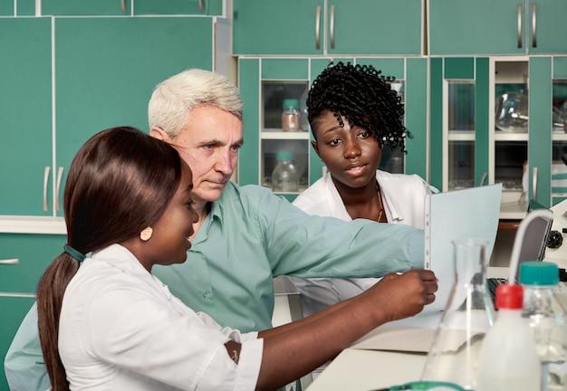 Vrouwelijke afrikaanse medische studenten of jonge afgestudeerden bespreken met blanke senor mannelijke groepsleider in onderzoek of medisch laboratorium. op zoek naar medicijnen, vaccin tegen coronavirus ontwikkelen.