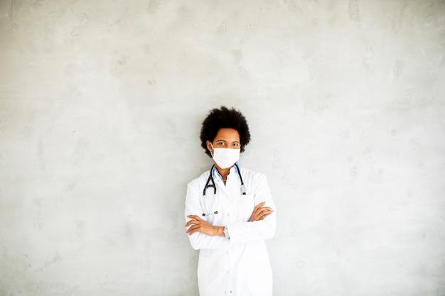 Vrouwelijke afro-amerikaanse arts draagt een wit uniform en beschermend gezichtsmasker in het ziekenhuis