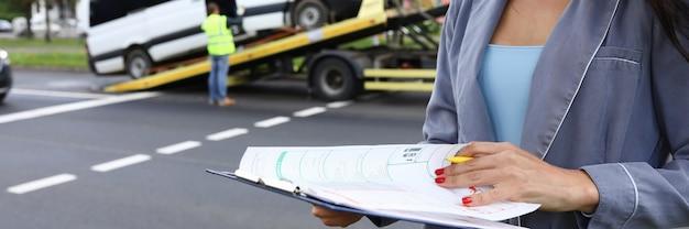 Vrouwelijke agent sluit een verzekering af op de plaats van het ongeval. diensten van verzekeringsmaatschappijen concept