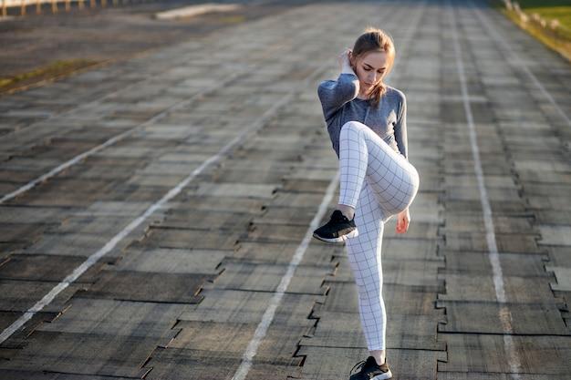 Vrouwelijke agent uitrekkende benen op renbaan