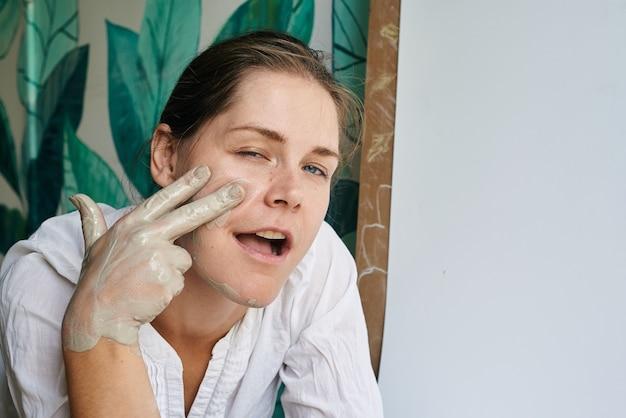 Vrouwelijke ambachtelijke keramist met handen gekleurd met grijze klei-looks en grijns