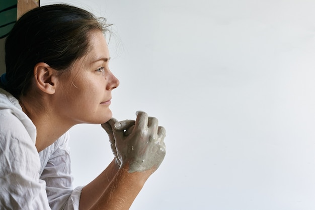Vrouwelijke ambachtelijke keramist met handen ingesmeerd met grijze klei