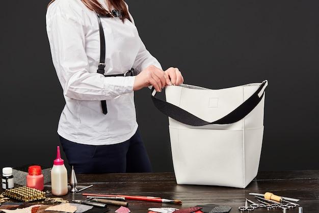 Vrouwelijke ambachtsman die riem vastmaakt aan witte handtas op de werkplek