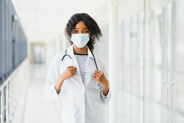 Vrouwelijke amerikaanse afrikaanse arts, verpleegstersvrouw die medische laag met stethoscoop en masker draagt. blij opgewonden voor succes medische werker poseren op lichte achtergrond. pandemie-concept, covid 19