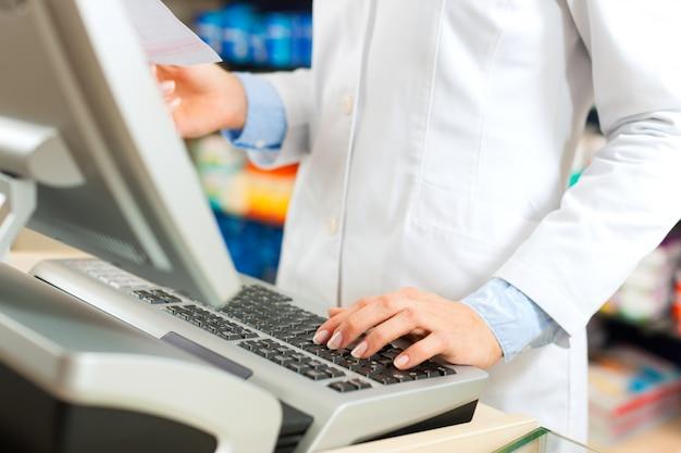 Vrouwelijke apotheker bij de kassier in de apotheek