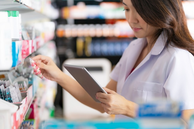 Vrouwelijke apotheker die een medicijn uit de plank neemt en digitale tablet gebruikt in de apotheek