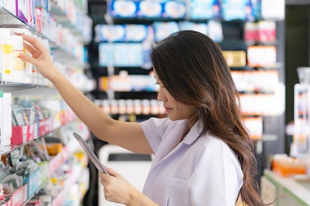 Vrouwelijke apotheker die een medicijn uit de plank neemt en digitale tablet in de apotheek gebruikt