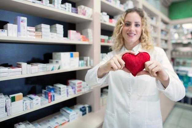 Vrouwelijke apotheker die hart houdt en cardiovasculaire medicijnen en succesvolle behandeling promoot