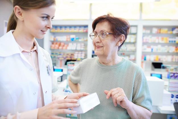 Vrouwelijke apotheker die hogere vrouw bijstaat