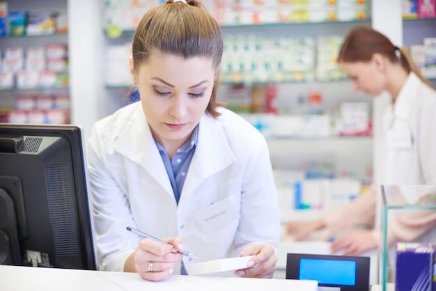 Vrouwelijke apotheker die in drogisterij werkt