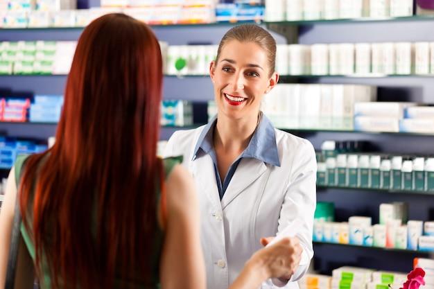 Vrouwelijke apotheker in haar apotheek met een klant