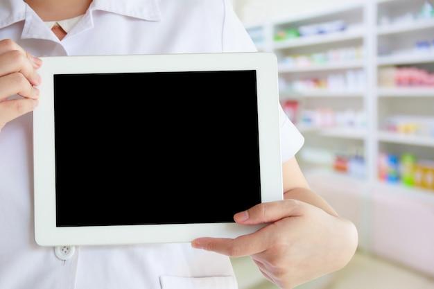Vrouwelijke apotheker met behulp van tablet pc tegen close-up van planken van drugs