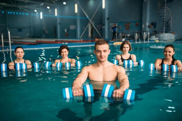 Vrouwelijke aqua-aerobicsgroep en mannelijke trainer doen oefening met halters op training in zwembad. fitnesstraining, watersport