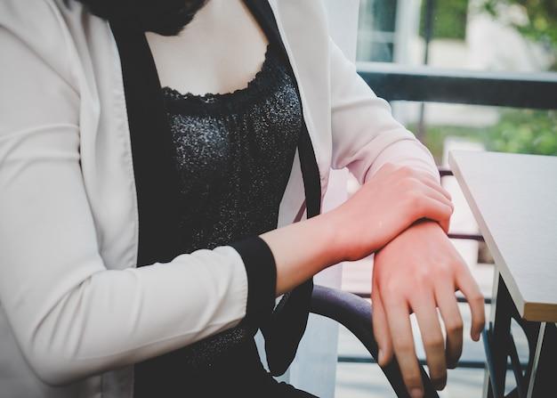 Vrouwelijke arbeider die de schade van het bureausyndroom op haar pols handwortele tunnel heeft