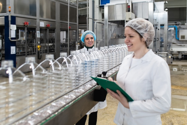 Vrouwelijke arbeiders in bottelarij die waterflessen controleren vóór verzending. inspectie kwaliteitscontrole.