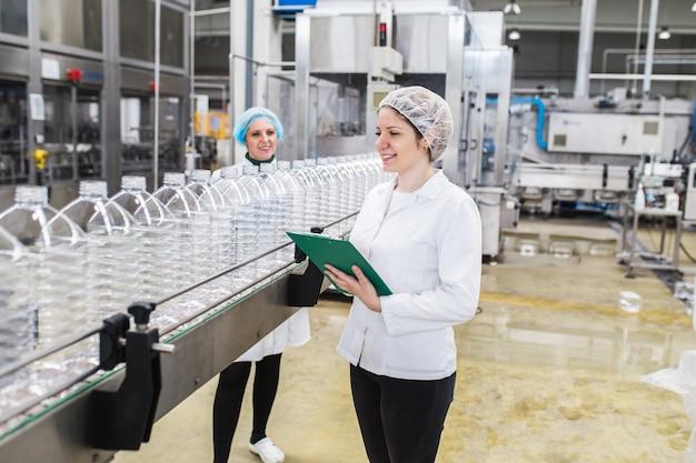Vrouwelijke arbeiders in bottelarij die waterflessen controleren vóór verzending