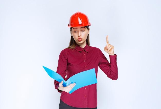 Vrouwelijke architect die in rode helm blauwe omslag op witte achtergrond leest.