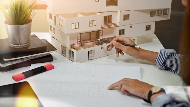 Vrouwelijke architect die met modelhuis en blauwdruk in huisbureau werkt.
