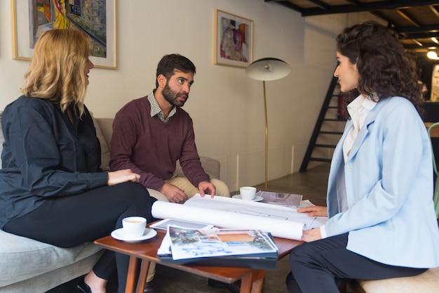 Vrouwelijke architect die plattegrond voorstelt en blauwdruk bespreekt