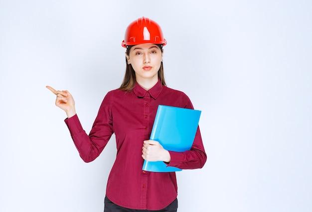 Vrouwelijke architect in rode helm met blauwe map die staat en poseert.