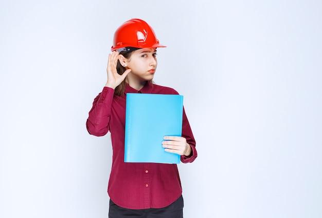 Vrouwelijke architect in rode helm met blauwe map en poseren voor de camera.