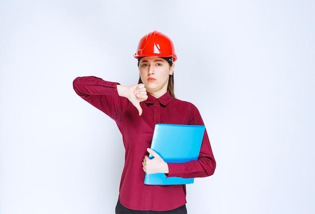 Vrouwelijke architect in rode helm met blauwe map met documenten en duimen naar beneden.