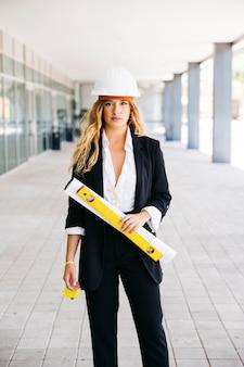 Vrouwelijke architect met helm en plan