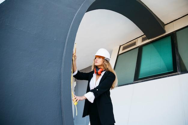 Vrouwelijke architect op bouwplaats met niveau
