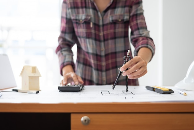 Vrouwelijke architect tekening blauwdrukken op kantoor werkplek.