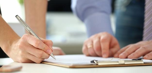 Vrouwelijke arm biedt contractvorm op klembordkussen