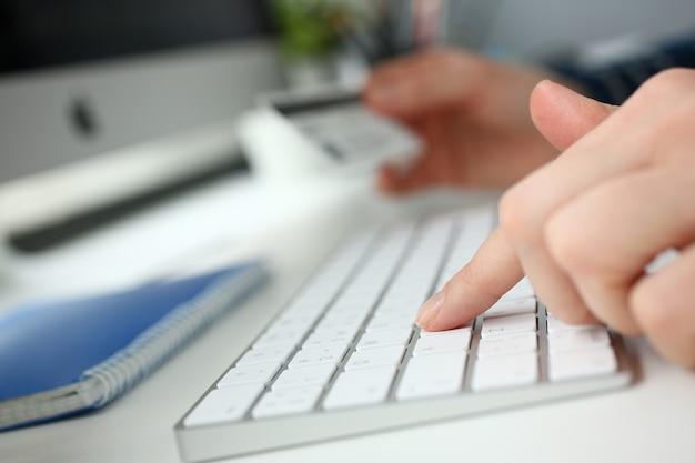 Vrouwelijke armen houden creditcard drukknoppen