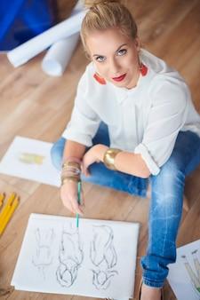 Vrouwelijke artiest die modeschetsen maakt