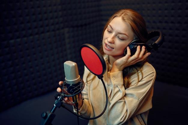Vrouwelijke artiest in koptelefoon zingt een lied op microfoon, opnamestudio interieur op achtergrond. professionele spraakopname, werkplek voor muzikanten, creatief proces, moderne audiotechnologie