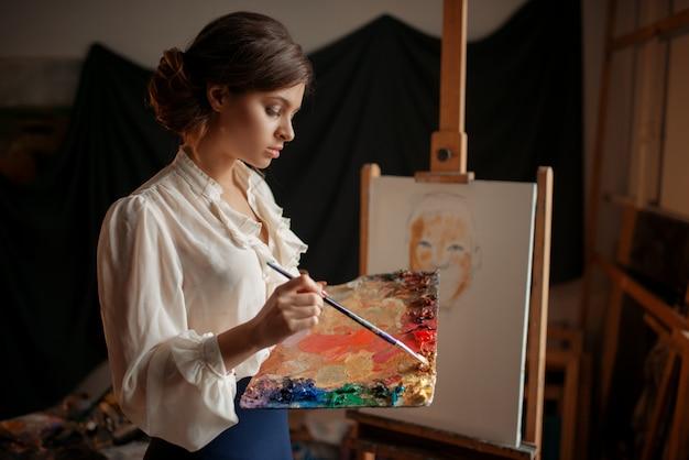 Vrouwelijke artiest met kleurenpalet en penseel staande tegen ezel in studio. creatieve verf, portretschilder, atelierinterieur op achtergrond
