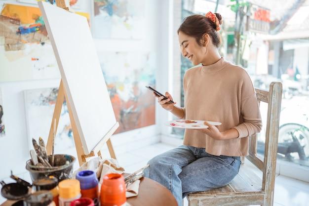 Vrouwelijke artiest op zoek naar inspiratie van haar mobiele telefoon