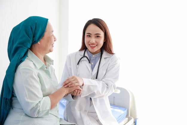 Vrouwelijke arts aanmoedigen met kanker aan de patiënt in medisch kantoor. ondersteun mensen met een tumorziekte.
