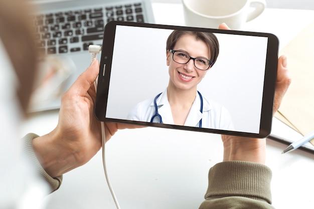 Vrouwelijke arts adviseert patiënt online videochatten.