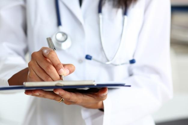 Vrouwelijke arts arm houden zilveren pen vullen