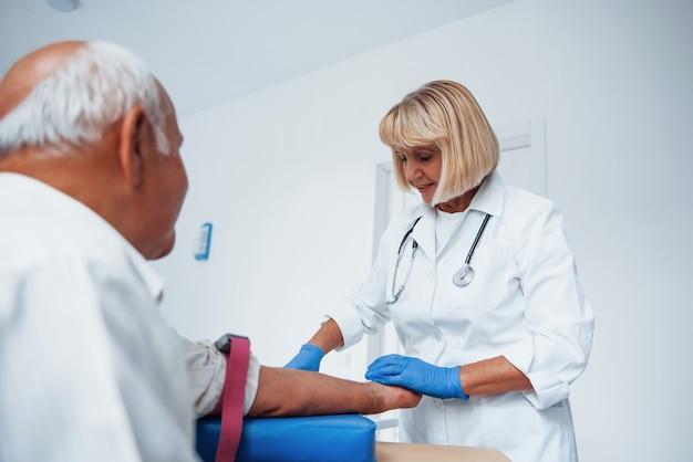 Vrouwelijke arts bereidt zich voor op het injecteren van senior mannelijke patiënt in de kliniek.