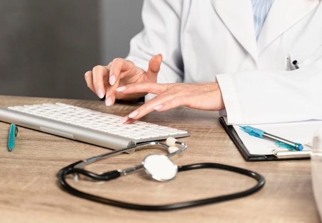Vrouwelijke arts bij haar bureau dat op toetsenbord schrijft