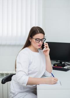 Vrouwelijke arts bril en een witte medische jas zit aan haar bureau en maakt aantekeningen in een notitieblok