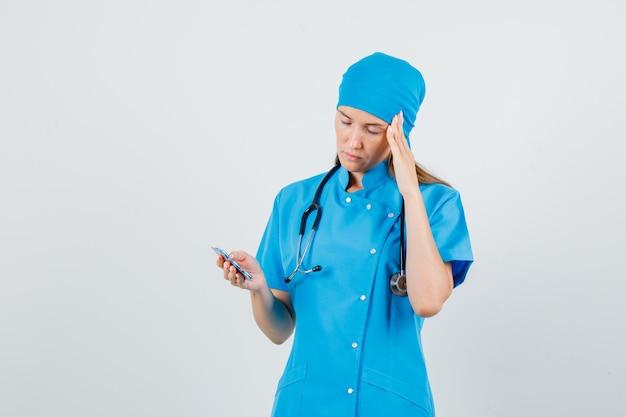 Vrouwelijke arts capsules met vingers op tempels in blauw uniform houden en op zoek pijnlijk. vooraanzicht.