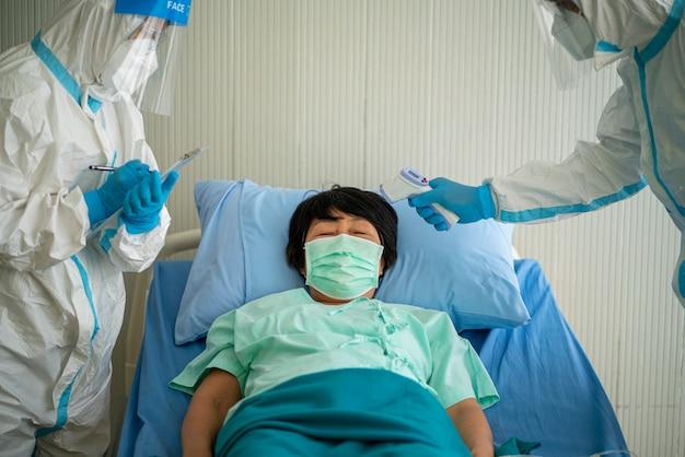 Vrouwelijke arts controleert aziatische vrouw lichaamstemperatuur met behulp van infrarood voorhoofdthermometer (infrarood thermometer) voor virussymptomen in het ziekenhuis. coronavirus, covid-19, quarantaine of virusuitbraakconcept