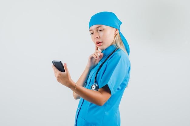 Vrouwelijke arts denken tijdens het kijken naar smartphone in blauw uniform