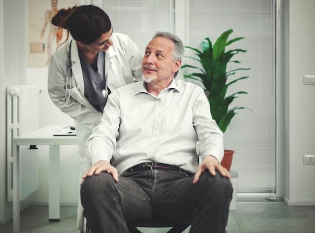 Vrouwelijke arts die aan een patiënt op een rolstoel spreekt