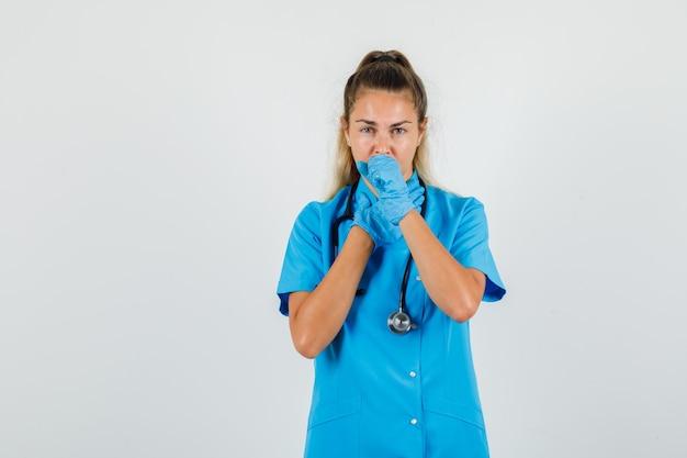 Vrouwelijke arts die aan hoest in blauw uniform lijdt